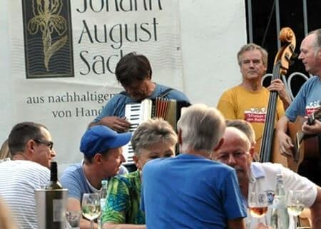 Leute sitzen an Tischen und trinken Wein. Eine Band spielt im Hintergrund