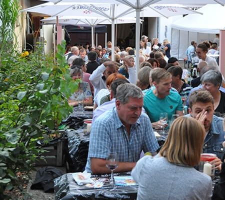 Besucher sitzen unter Sonnenschirmen im Hof des Weinguts und trinken Wein.
